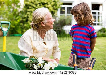 Smiling granny with grandson near flower pot in wheelbarrow at yard