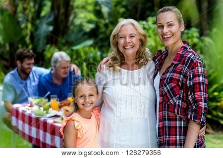 Portrait of mother with daughter and granny standing at yard