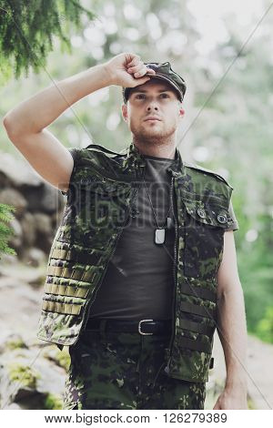 war, army and people concept - young soldier or ranger wearing military uniform in forest