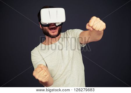 Beard man driving in virtual reality wearing hi-tech VR headset, on black background