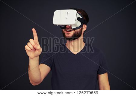 Man in black t-shirt touch something with his right hand using virtual reality glasses, on black background