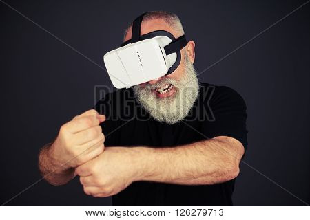 Senior man clenches his fists and his teeth in virtual reality wearing hi-tech VR headset