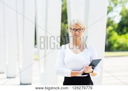 22.Cute female office manager being outdoor with a tablet.