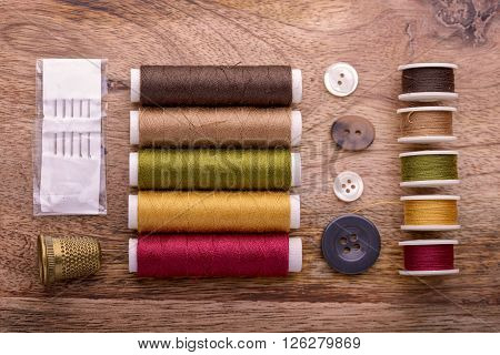 cotton sewing autumn color with buttons, needles and thimble on wood