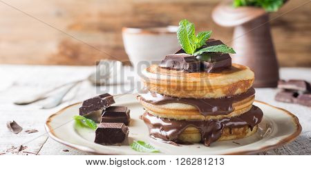 Homemade pancakes with chocolate spread and mint. Healthy breakfast concept.