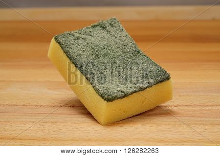 Worn out Srubber on wooden background yellow sponge with scrubber