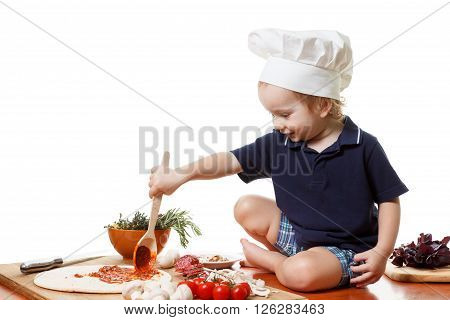 Little caucasian boy in the cook cap helps mum to cook a pizza. Closeup isolated on white background