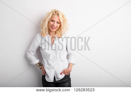 Shy woman leaning against white wall with her hands in pockets