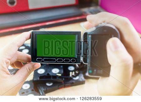 Hand and video camera recording cassette tapes in office background
