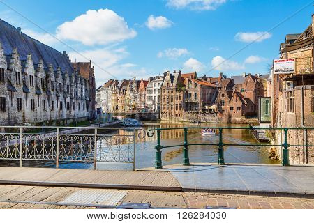 Ghent, Belgium - April 12, 2016: View of old colorful traditional houses along the canal, part of bridge in popular touristic destination Ghent, Belgium