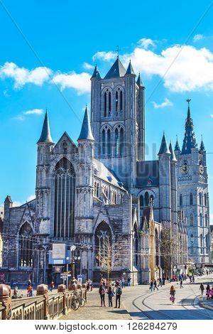 Ghent, Belgium - April 12, 2016: Vibrant color street view of Ghent, Belgium with St Nicholas' Church, beautiful houses and people near it