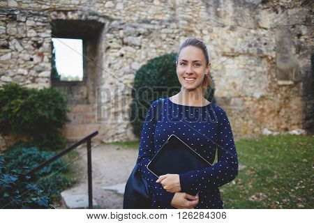 Smiling gorgeous woman tourist with portable digital tablet in hands and rucksack on back is posing for photos on the memory during excursion while standing against the wall of historical old castle