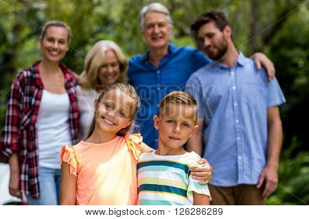 Portrait of happy multi-generation family standing in yard