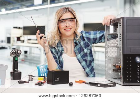 Young female PC technician posing seated at a desk in an office