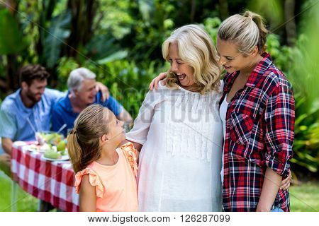 Happy mother and granny looking at girl standing in yard