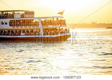 ISTANBUL - MAY 28, 2015: Ferry full with tourists floats on Bosphorus waterway in Istanbul on the sunset. Ferry in Istanbul is very popular transport connecting European and Asian part of the city