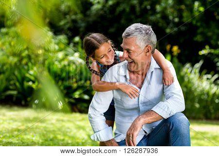 Happy grandfather and grandaughter playing at yard