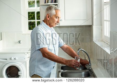 Calm senior man filling water in glass while standing at sink in kitchen