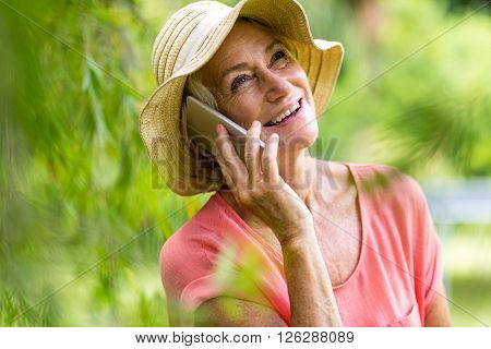Senior woman using phone while standing in yard