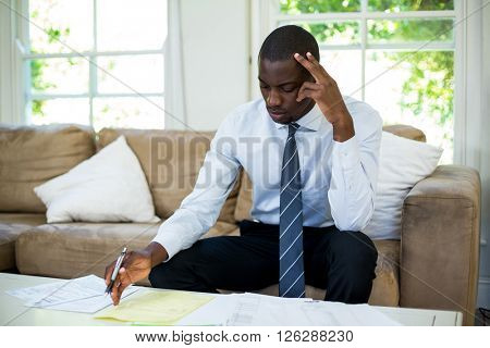Tensed man sitting on sofa and accounting the bills at home