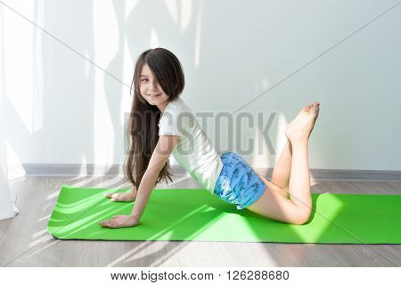 little girl doing gymnastics on a green yoga mat. children's fitness and yoga for children. fitness exercises and stretching.