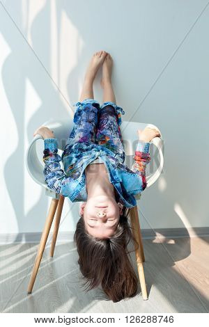Portrait of a little girl of fashion baby on a white chair. Stylish little girl with long hair is sitting upside down, hanging his head down. Photo model child cool fashionable. Carefree fun