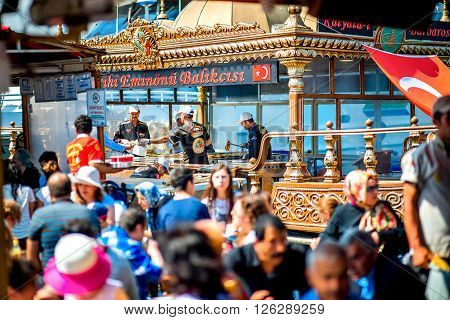 ISTANBUL - MAY 28, 2015: Crowded place near Golden Horn coast and Galata bridge with popular turkish buffet on boats with fish sandwiches. This place is very famous with lots of restaurants and cafe.
