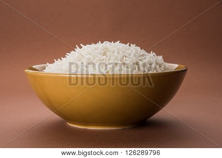 basmati rice in a brass bowl, cooked basmati rice, cooked plain rice, cooked white basmati rice, steamed basmati rice served in a ceramic bowl