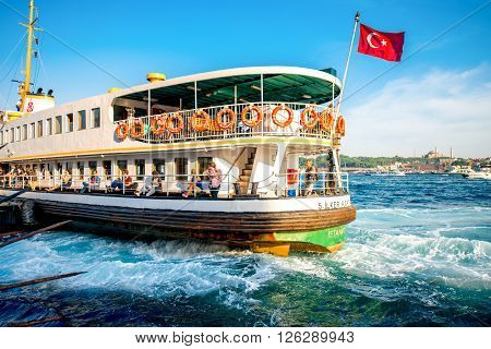ISTANBUL - MAY 28, 2015: Ferry full with tourists floats on Bosphorus waterway in Istanbul on the sunset. Ferry in Istanbul is very popular transportation between European and Asian part of the city