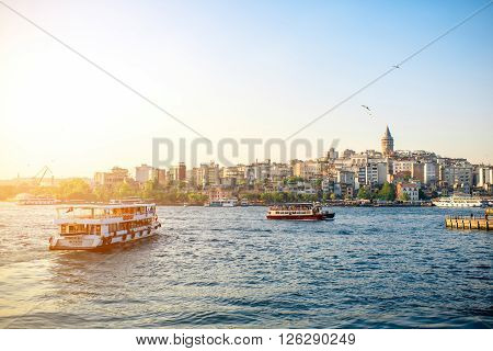 ISTANBUL - MAY 28, 2015: Ferries float on Bosphorus waterway with Galata tower on the background in Istanbul on the sunset. Ferry in Istanbul is very popular transportation.