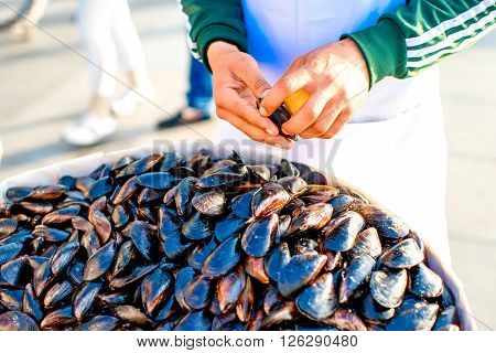 ISTANBUL - MAY 28, 2015: Male hands cleans mussels for quick snackfood in Istanbul. Mussels is very popular street food in Istanbul selling one by one to the tourists