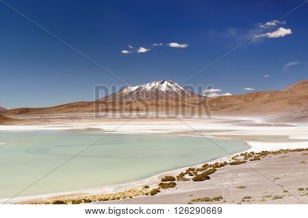 South America - Bolivia. The surreal landscape is nearly treeless punctuated by gentle hills and volcanoes near Chilean border. The picture present lagoon Kota