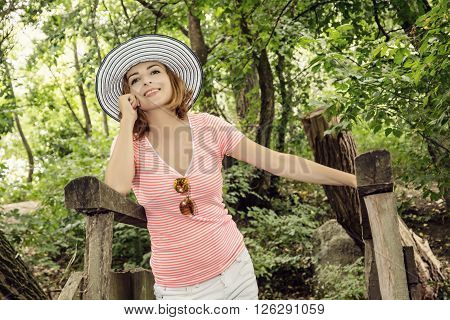 Young youful woman with sunhat posing in green forest. Beauty and nature.