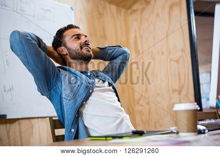 Man relaxing on chair with hands behind head in office