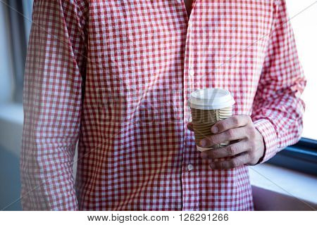 Mid section man holding disposable cup of coffee in office