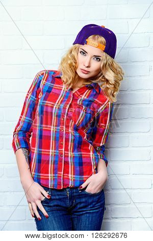 Beautiful modern girl with curly blonde hair wearing baseball cap and checkered shirt posing by a brick wall.