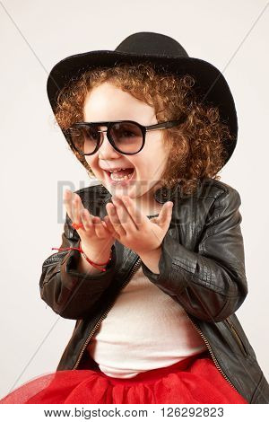 Little girl with black hat and Sunglass sitting and laughing