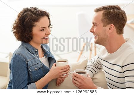 Relieve stress. Cheerful positive smiling couple sitting on the couch and  talking while drinking coffee