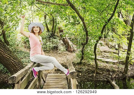 Young caucasian woman with stylish sunhat is sitting on the wooden bridge in the forest. Beauty and nature.