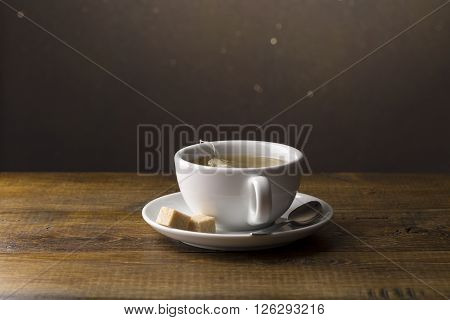 Tea cup with tea bag on saucer.Wooden background