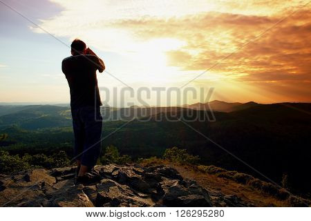 Professional Photographer In Jeans And Shirt  Takes Photos With Mirror Camera On Peak Of Rock. Dream