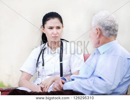 Young Nurse With Senior Man In Courtyard