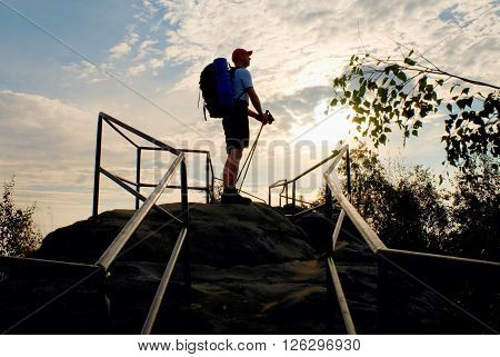 Tall Backpacker With Poles In Hand. Sunny Spring Daybreak In Rocky Mountains. Hiker With Big Backpac
