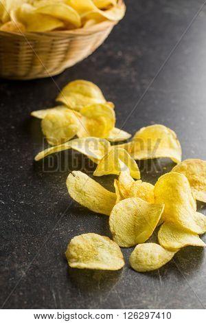 Crispy potato chips on old kitchen table