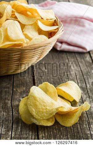Crispy potato chips on old kitchen table