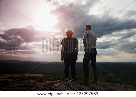 Couple enjoying marvellous moments during sunset . Young pair of hikers on the peak of rock empires park and watch over valley to Sun.