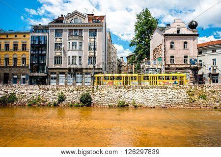 SARAJEVO, BOSNIA and HERZOGOVINA - CIRCA JUNE 2015: Central street near Miljacka river with old yellow tram in Skopje.