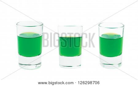 Small glass shot filled with the green colored liqueur alcohol drink, isolated over the white background, set of three different foreshortenings