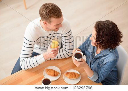Nice beginning of the day. Cheerful delighted positive loving couple having  breakfast   and talking while sitting at the table