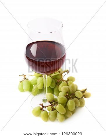Glass of red wine next to a branch of white table grapes isolated over the white background